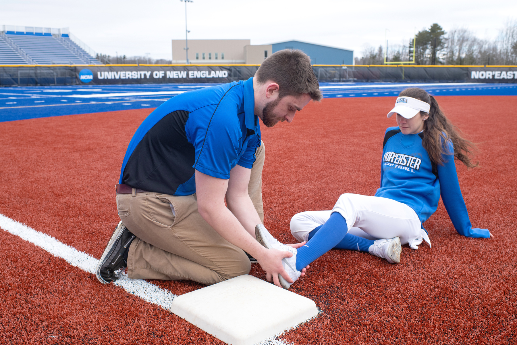 An athletic training student checks a fellow student's ankle on the baseball field