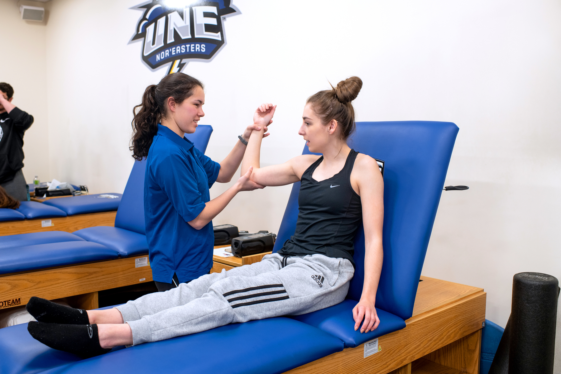 A female student performs a physical evaluation on a fellow student