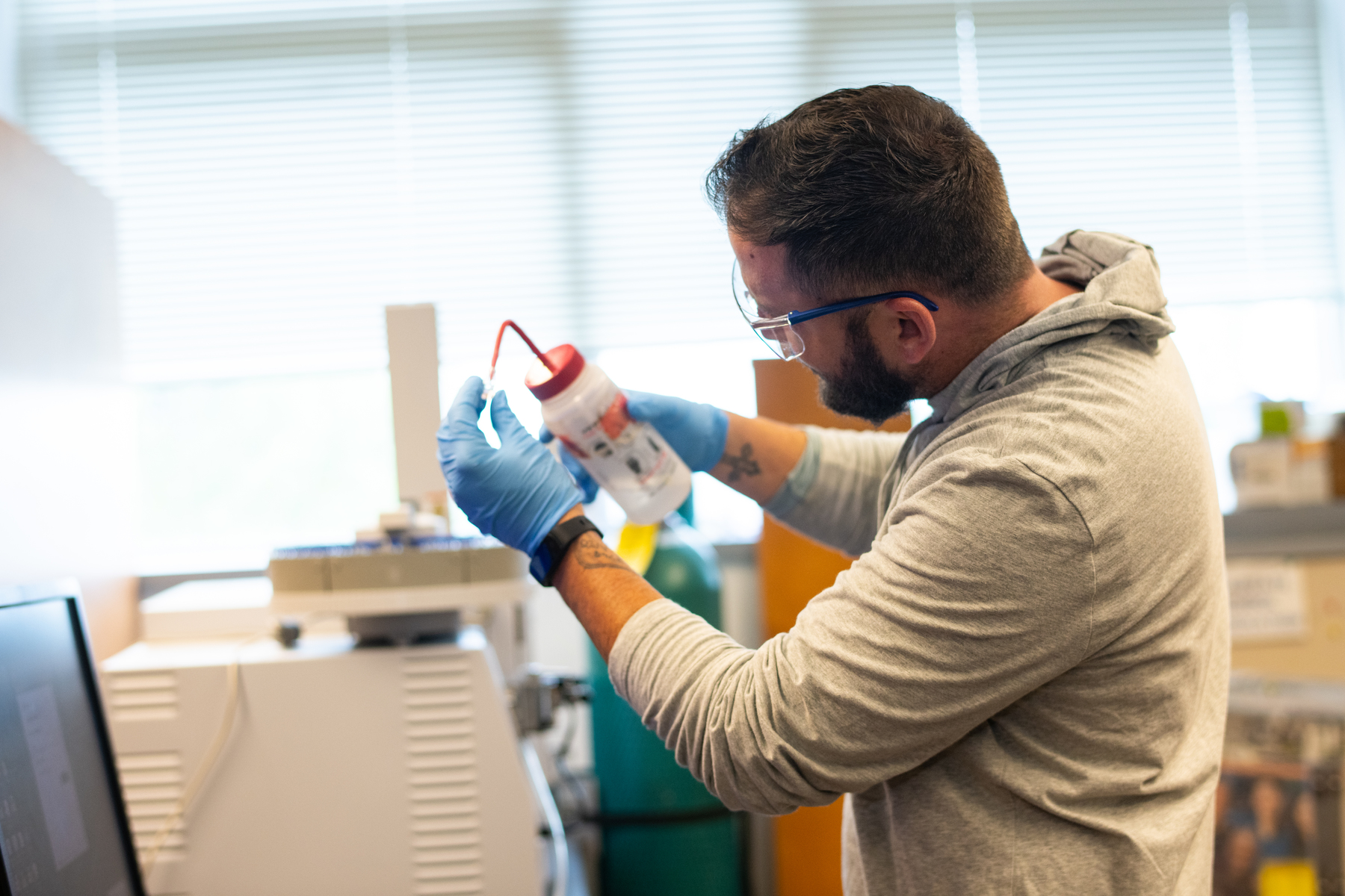 A male student works on an experiment in the biochemistry laboratory