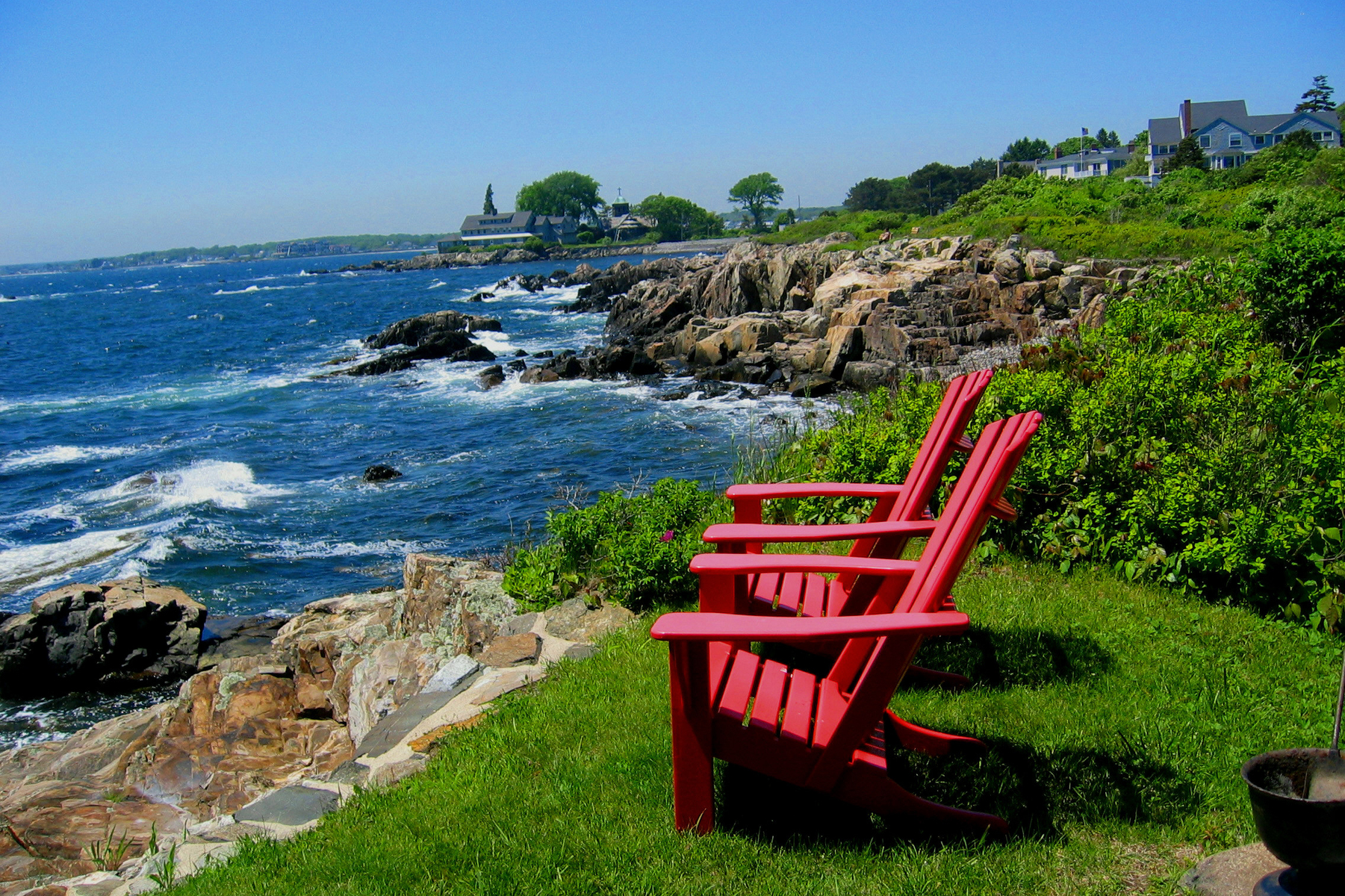Two Adirondack chairs on the coast of Maine