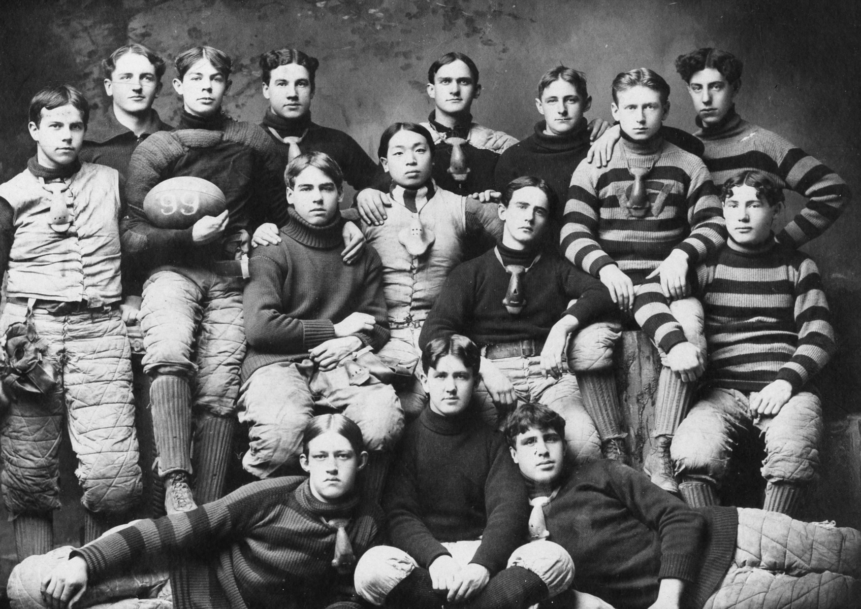 Black and white historic image of young men in rugby uniforms