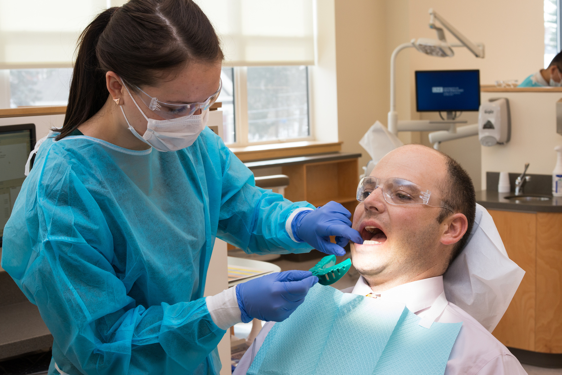 A U N E dental student inserts a green instrument into a patient's mouth