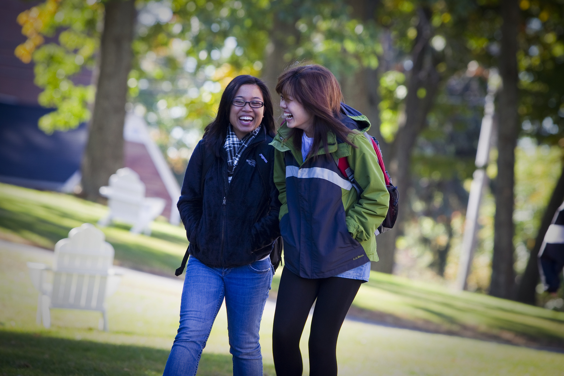Two students share a laugh as they walk on campus