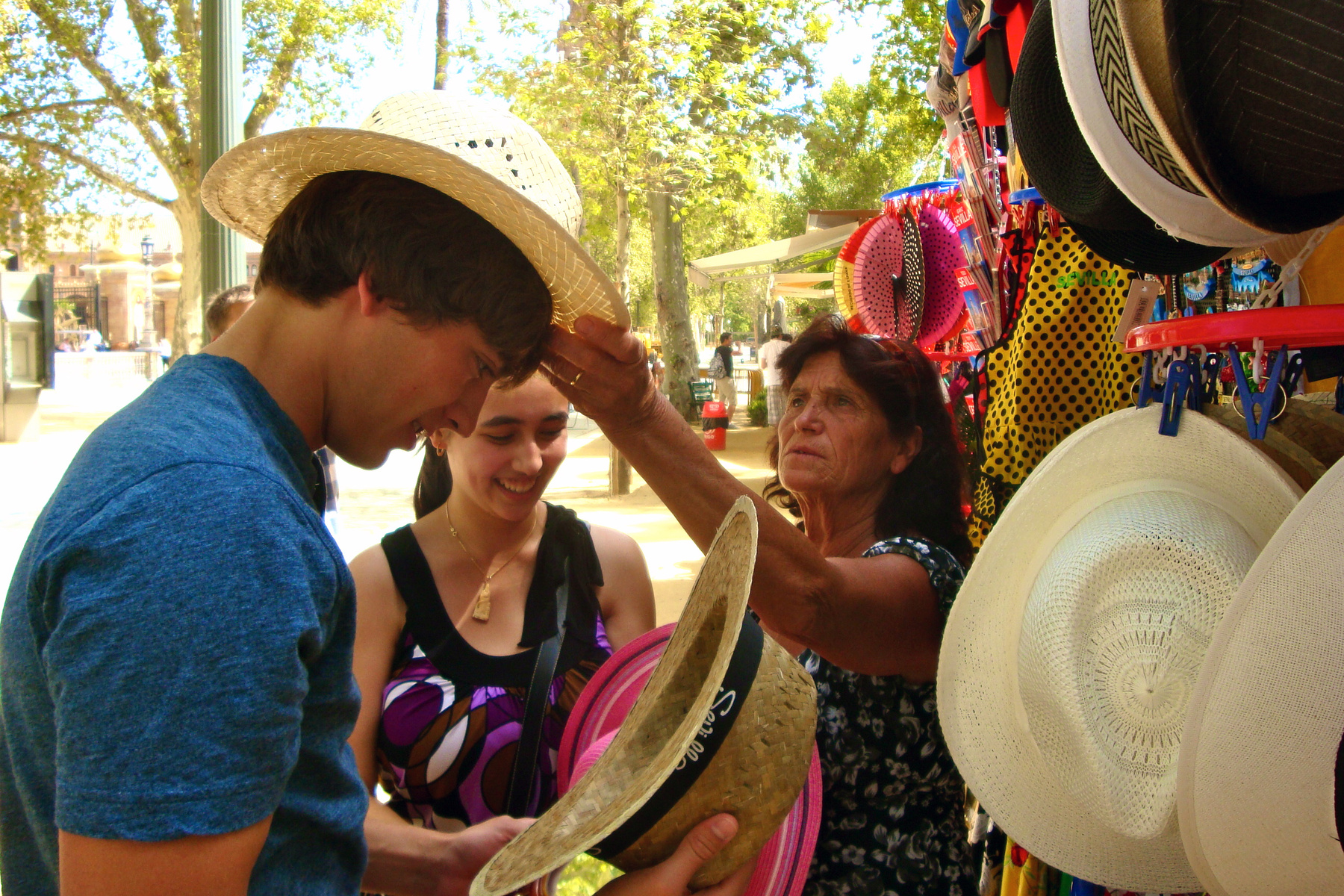 A U N E student interacts with a street vendor selling hats in Latin America