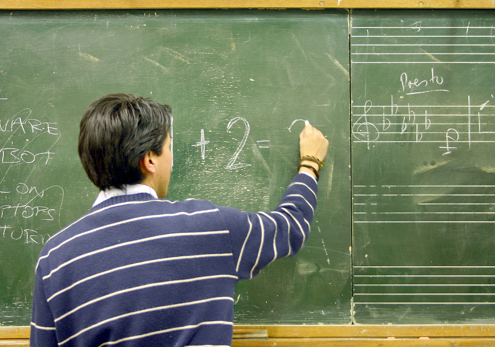 A male teacher writes a math equation on a chalkboard