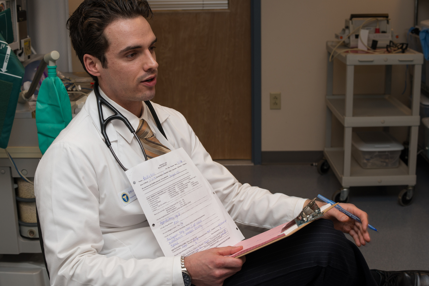 A U N E physician assistant student sits in a hospital room reviewing a patient's chart