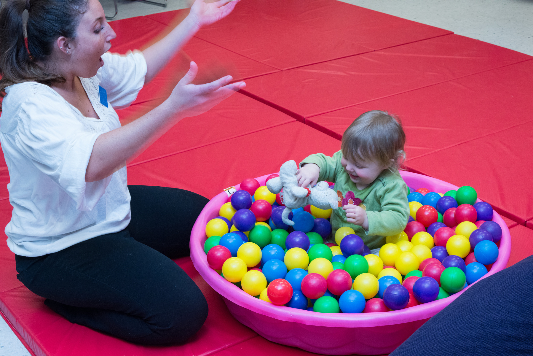 An Occupational Therapist plays with a toddler sitting in a pink wading pool full of plastic balls