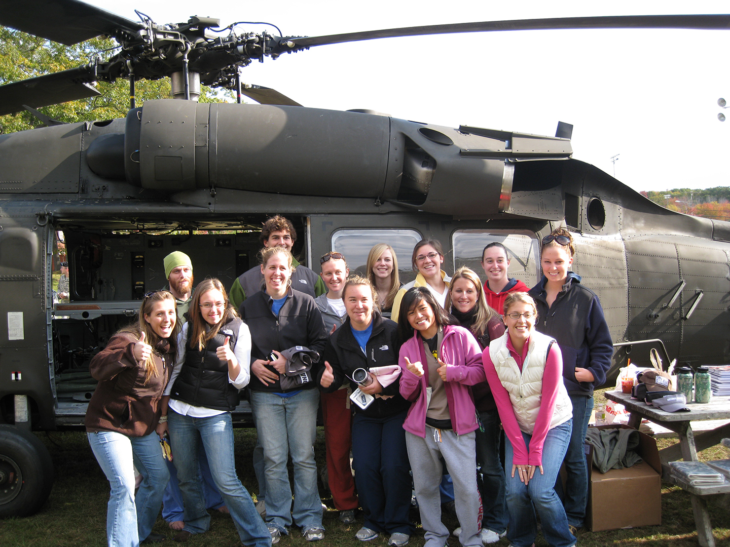 com students pose with a helicoptor