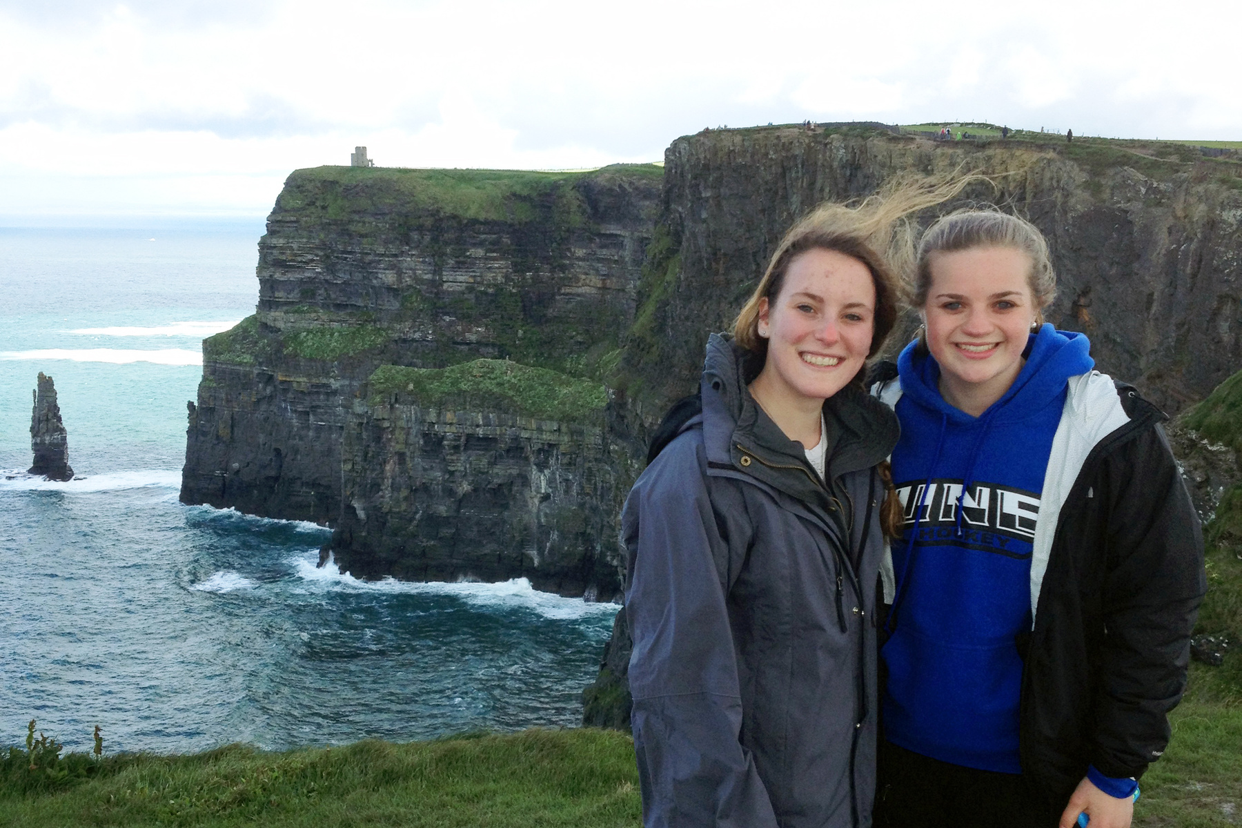Two female students pose on a seaside cliff in Ireland