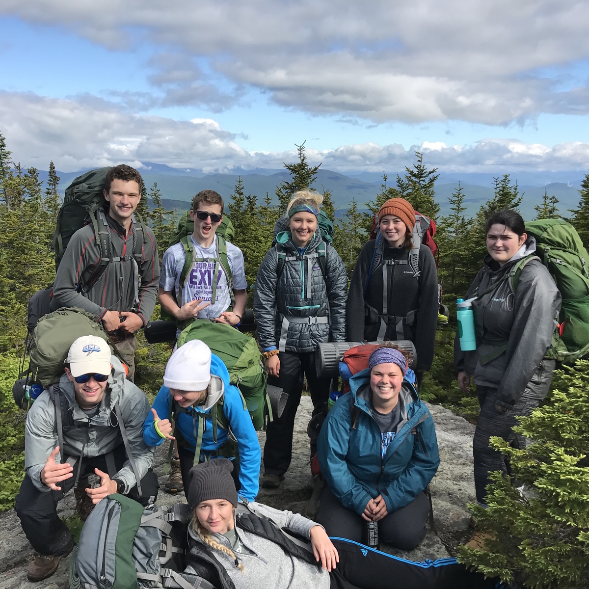 Students on a hike pose at the summit in the White Mountains