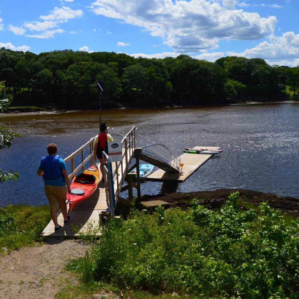 students launch kayaks from a dock