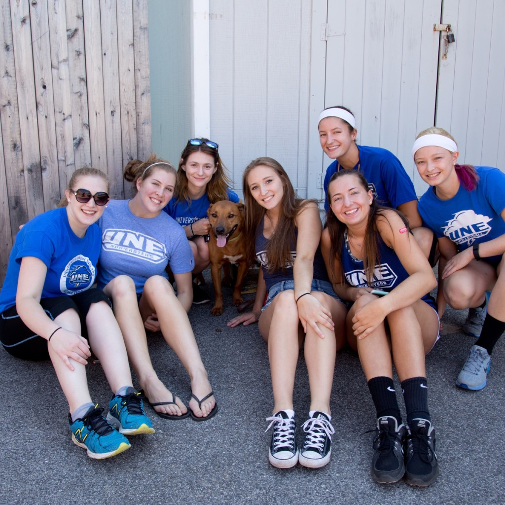 a group of students pose outside in matching blue u n e t-shirts with a dog