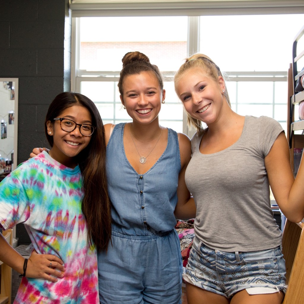 three female students pose in a dorm room