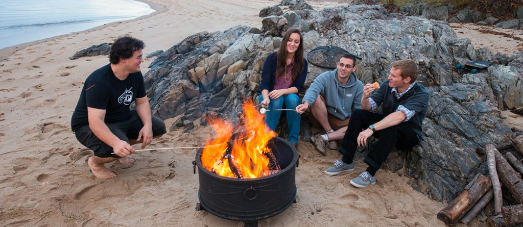 a group of students sit around a bonfire on the beach