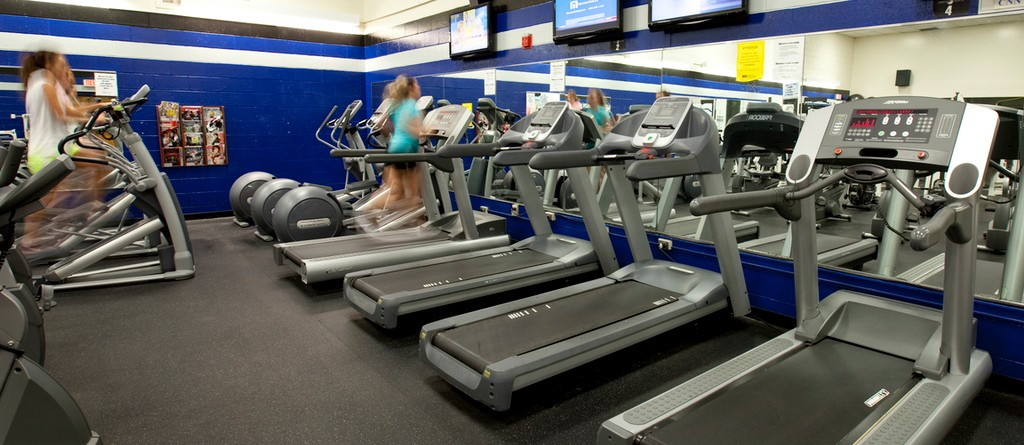 a row of treadills in the university fitness center with a student running on one