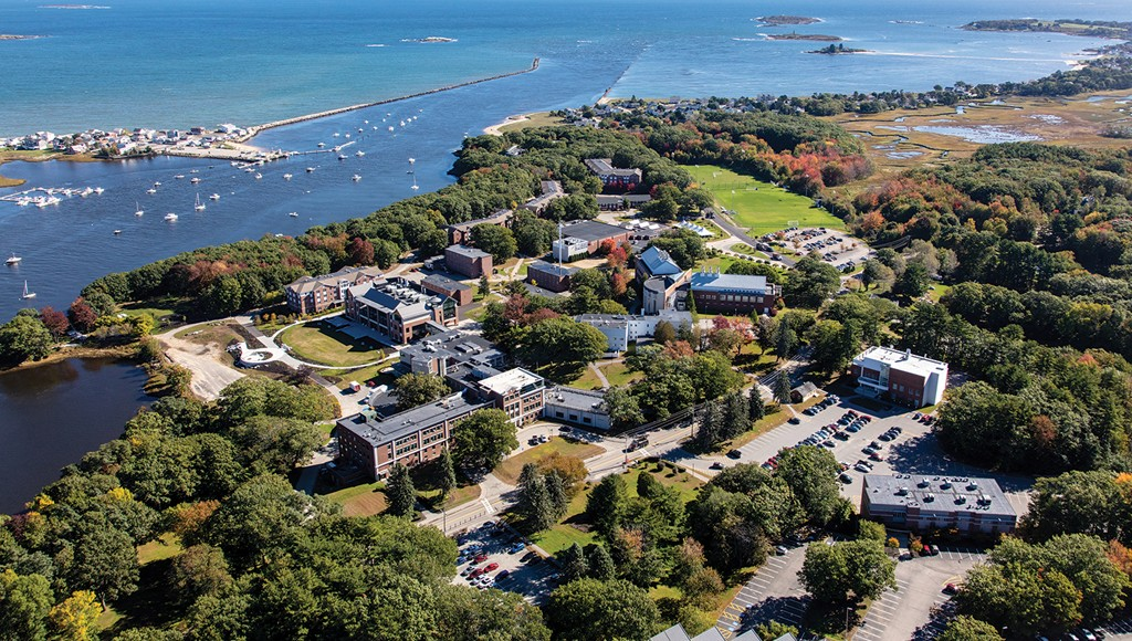 Aerial photo of U N E's Biddeford campus including buildings and the ocean