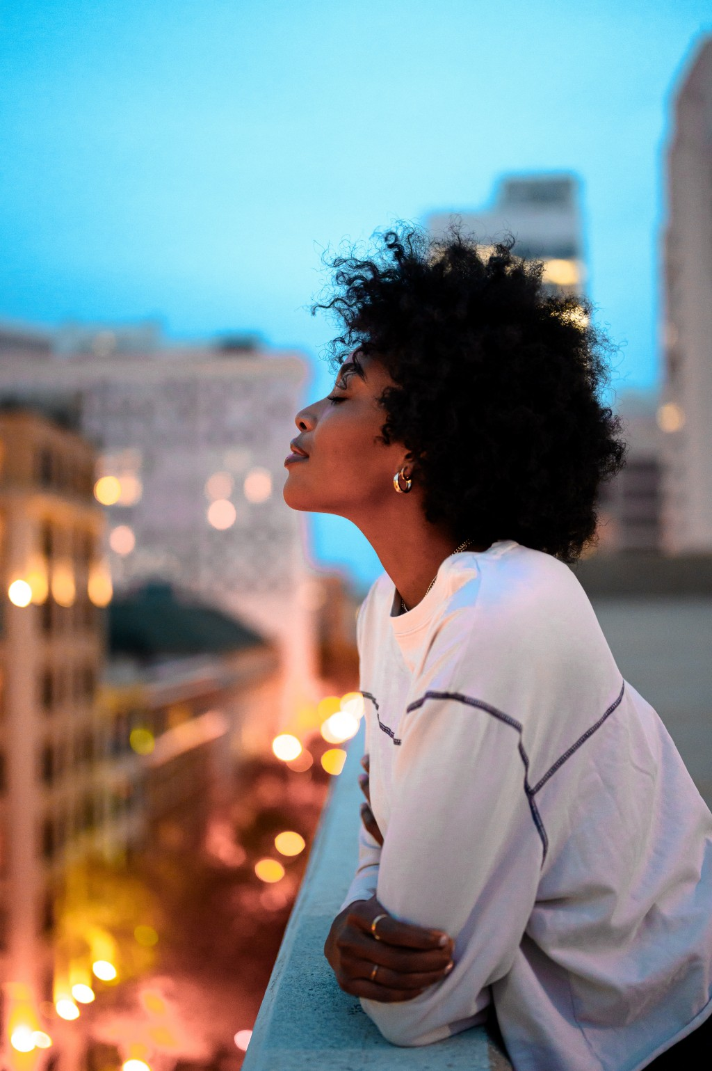 An African American woman stands on a city balcony at dusk
