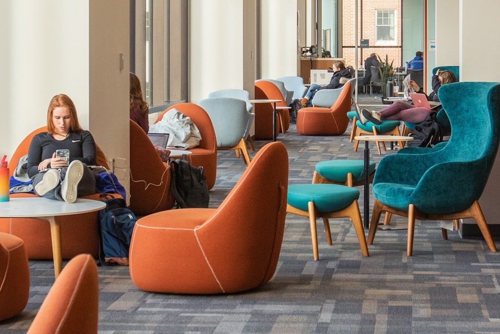 students relax in comfy chairs on the second floor of the Ripich Commons