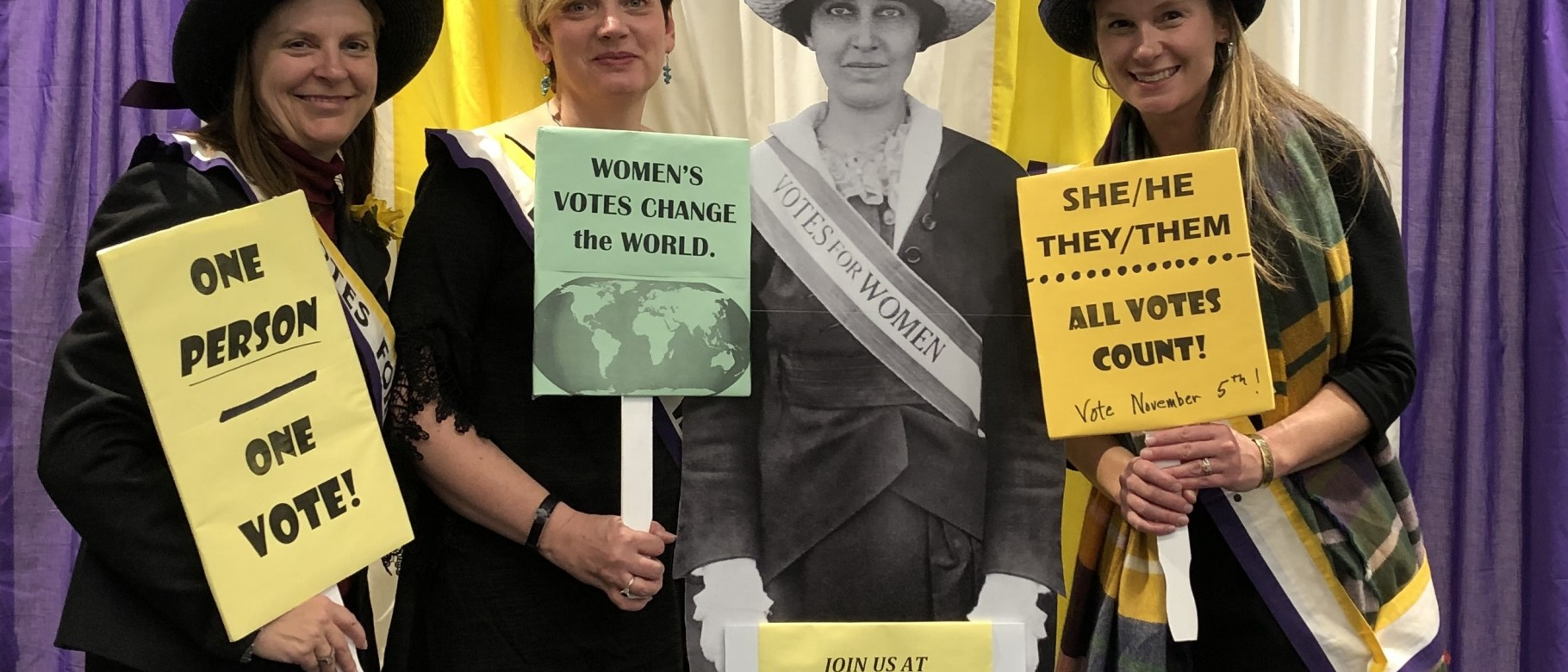 Attendees pose with an image of Katharine Dexter McCormick of the National Woman's Suffrage Association