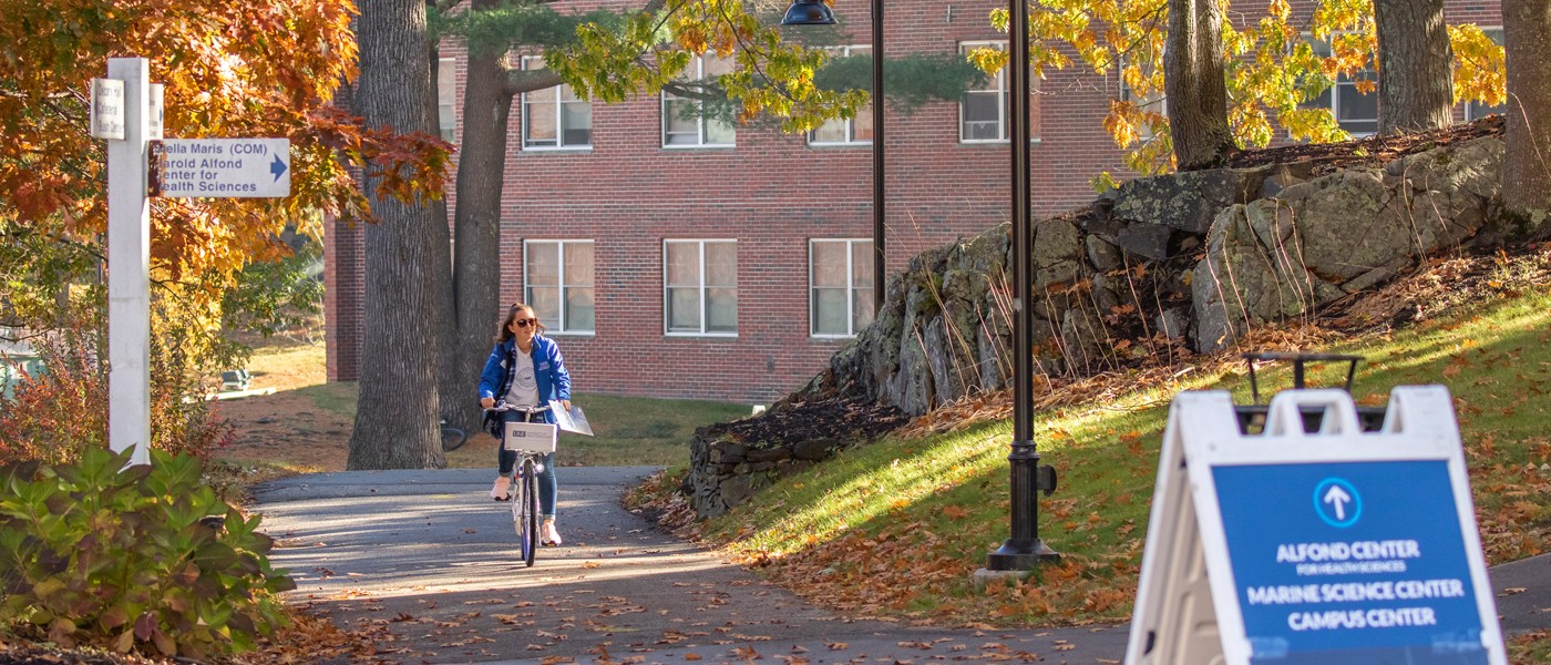 A student rides a bike through U N E's Biddeford campus during fall