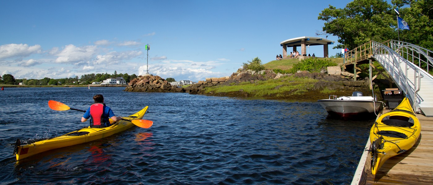 A student paddles a kayak in the ocean on U N E's Biddeford campus