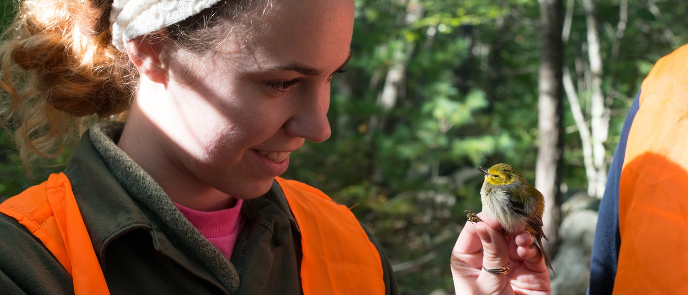 A female student looks at a small bird perched on her hand