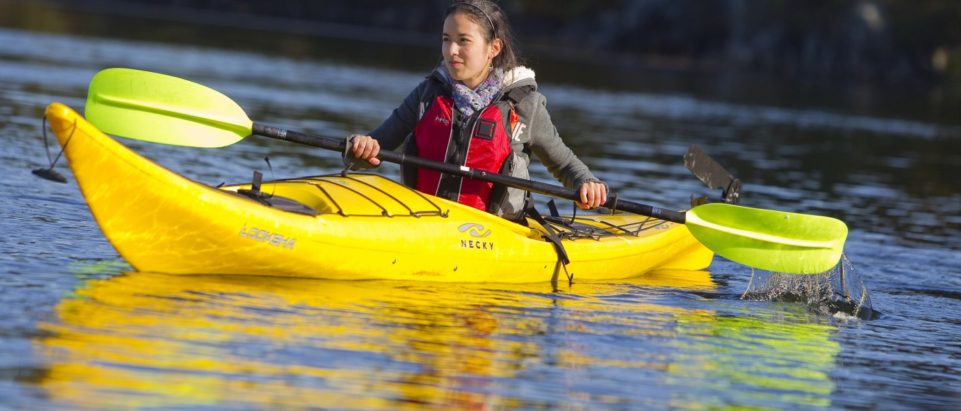 A U N E student paddles in a yellow kayak