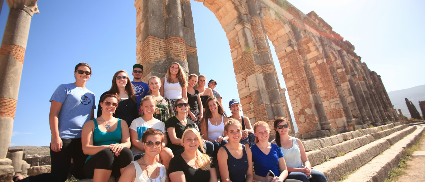 A group of U N E students sit on the steps by column ruins in Morocco