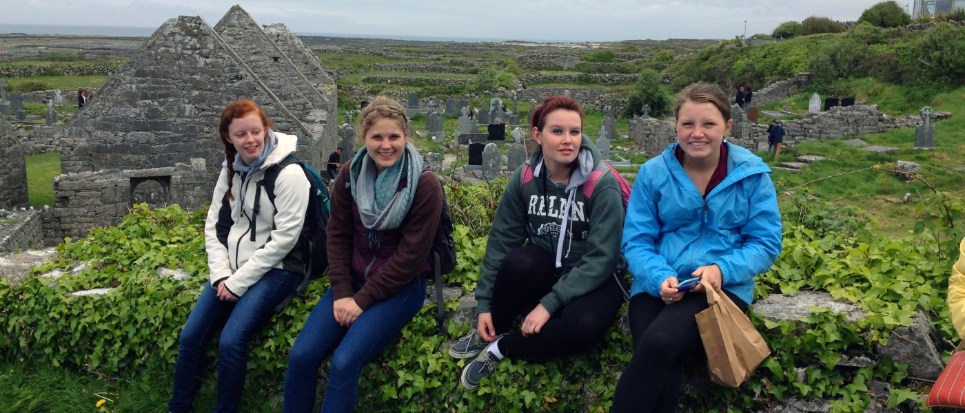 A group of U N E students sit on a stone wall at a rolling hillside cemetery in Ireland