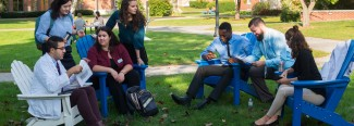 A group of graduate students sit outside in Adarondack chairs on the Portland campus quad