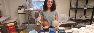 a female student holds pottery
