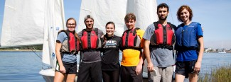 students wearing life vests in front of a sailboat