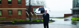 u n e president james herbert hold an umbrella while standing outside on campus in the rain